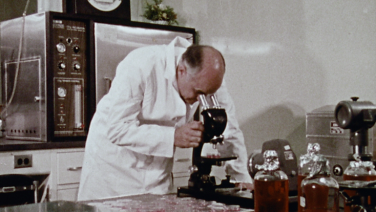 Dr. Hilleman and microscope